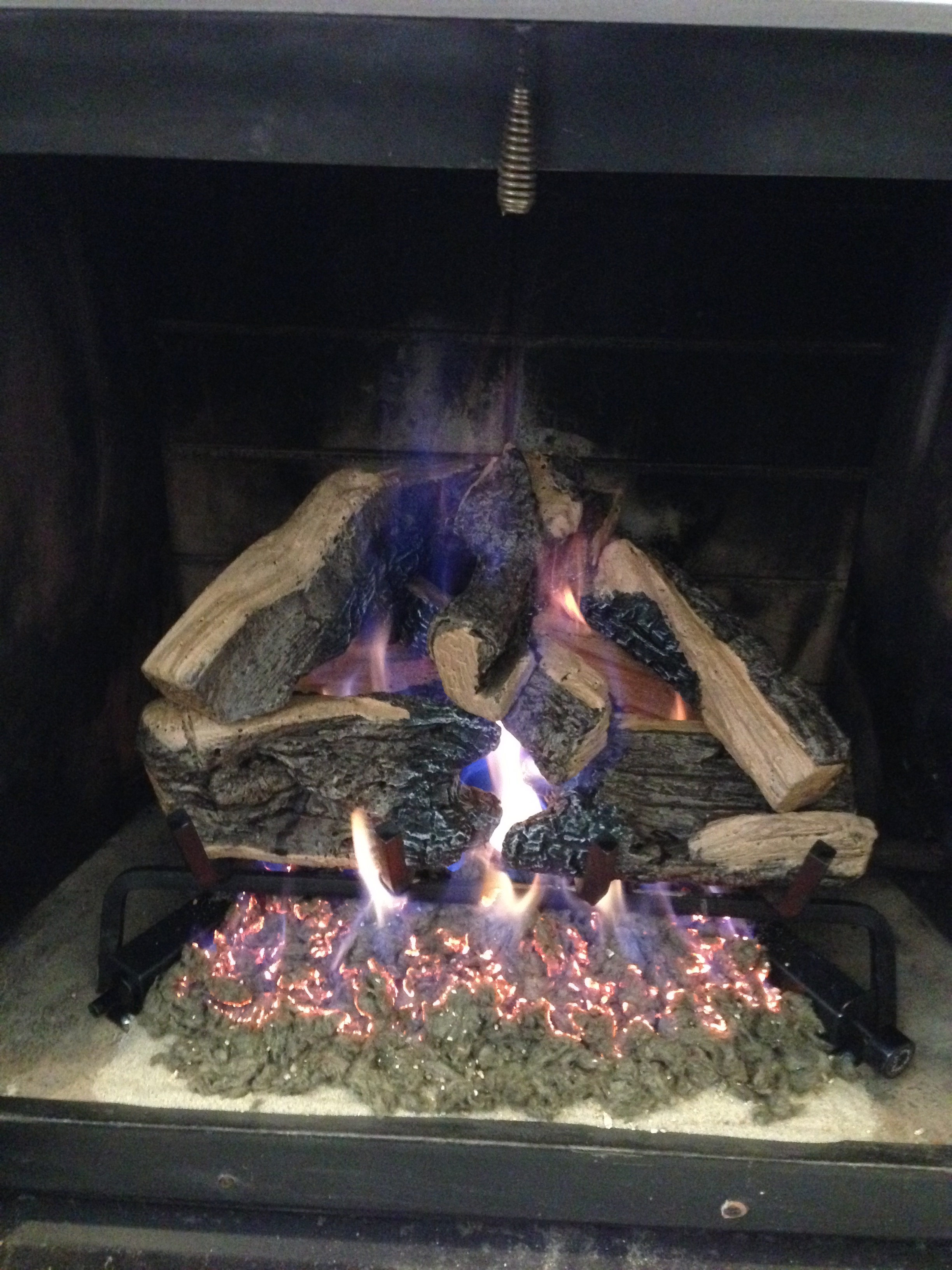 Photograph of burning logs in a gas fireplace.